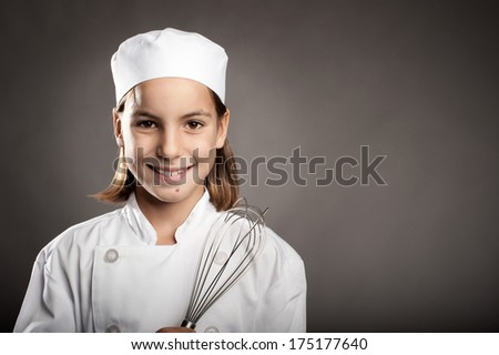 beautiful little chef cooking on gray background