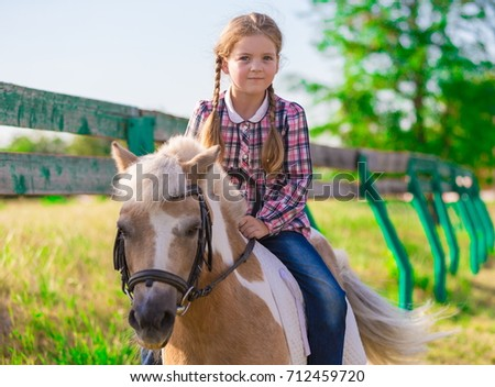 Beautiful little cowgirl riding horse pony. She has happy fun emotions, plaid shirt, blue jeans. Kids and animals family portrait. Nature amazing landscape in summer. Happy couple friends.