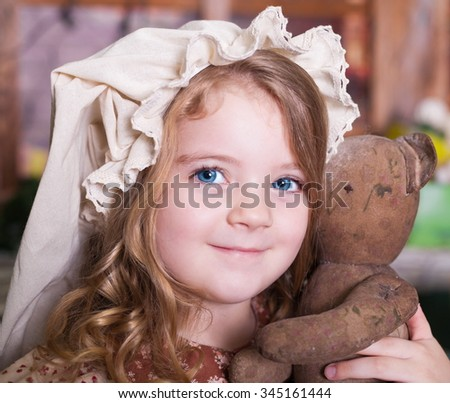 Beautiful little curly blonde girl, has happy fun cheerful smiling face, big blue eyes, white hat, holding a soft old toy. Portrait holiday Christmas.  - stock photo