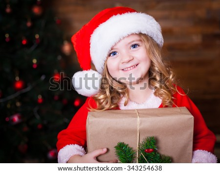 Beautiful little curly blonde girl, has happy fun cheerful smiling face, blue eyes, red Christmas hat Santa Claus, holding a gift box. Portrait holiday.  - stock photo