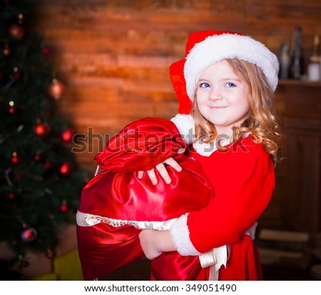 Beautiful little curly blonde girl, has happy fun cheerful smiling face, blue eyes, red Christmas hat, holding a gift box. Portrait holiday.  - stock photo