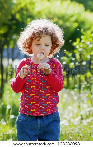 Beautiful little curly girl blowing dandelion, vertical  shot - stock photo