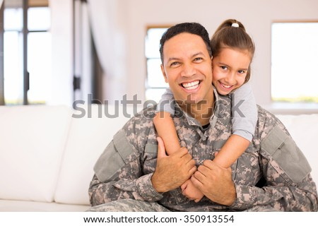 beautiful little daughter and military father at home - stock photo