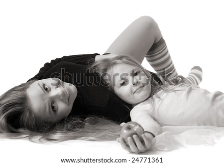 beautiful little daughter with apple lies on mum's stomach, isolated on white