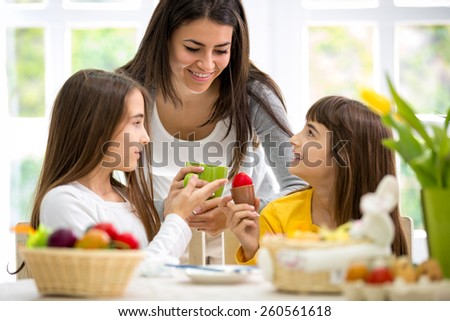 Beautiful little daughters showing mother painted Easter eggs - stock photo