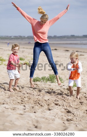 Beautiful little family playing together at the beach. The mother is jumping in the air while her children play around her.  - stock photo