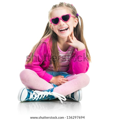 beautiful little fashion girl in gym shoes and skirt sit on a white background - stock photo