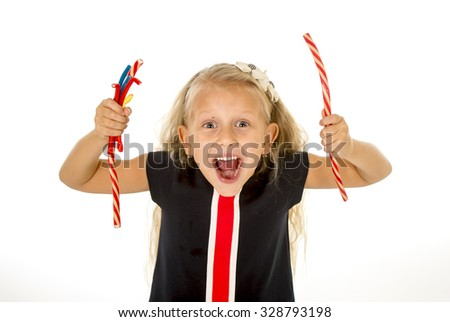 beautiful little female child with sweet blue eyes and long blond hair eating strawberry licorice candy and holding a bunch of gummies smiling happy isolated on white background - stock photo