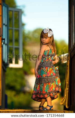 Beautiful little five-year girl posing for the camera on the porch of a village house at sunset - stock photo