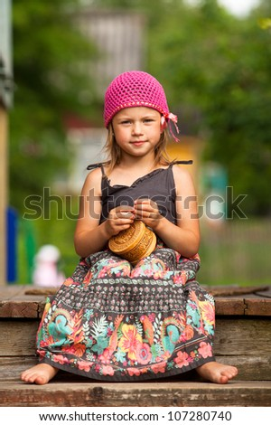 Beautiful little five-year girl sitting on the porch of a village house. - stock photo