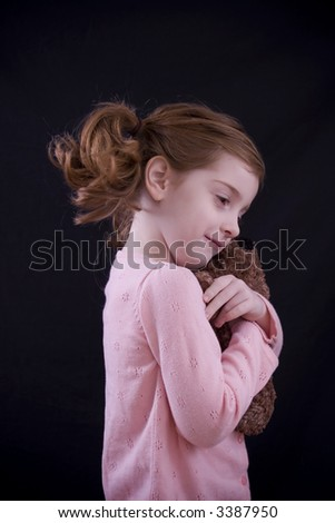 Beautiful little five year-old girl hugging her stuffed bear.