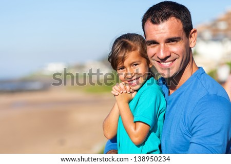 beautiful little girl and her father at the beach - stock photo
