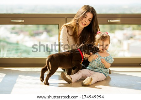 Beautiful little girl and her mom getting some puppy love and kisses from her new brown Labrador - stock photo