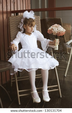 beautiful little girl as a bridesmaid sitting on the chair with the beautiful bouquet - stock photo