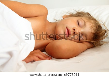 beautiful little girl asleep in bed on white sheet and pillow
