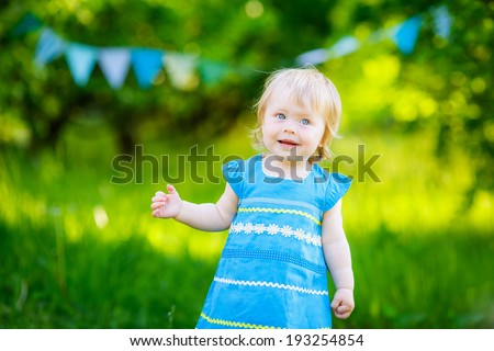 beautiful little girl blue dress on the nature