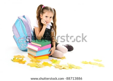 beautiful little girl, books and a backpack isolated on white