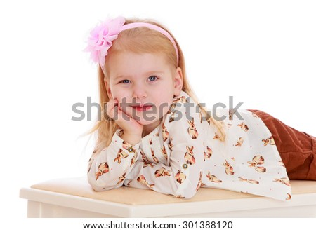 Beautiful little girl caucasian blond hair that holds the rim in the form of roses. Girl lying on the sofa leaning on her hand. She dressed lightweight summer shirt-Isolated on white background - stock photo