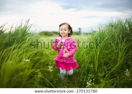 beautiful little girl cheerfully walking in green field in summer day. child playing outdoors. portrait of girl over green nature background - stock photo