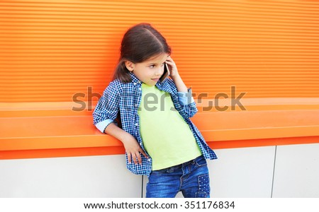 Beautiful little girl child talking on smartphone in city over colorful background - stock photo