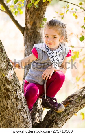 Beautiful little girl climbing on a tree outdoors.