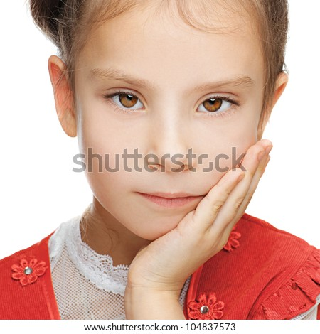 Beautiful little girl close up in red dress put her hand to cheek, isolated on white background.