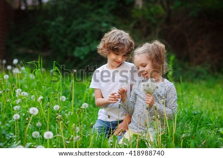 Beautiful little girl collects dandelions in the yard and boy want to present her flower.