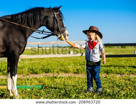 beautiful little girl cowboy feeding a horse carrot on a background of green grass and blue sky - stock photo