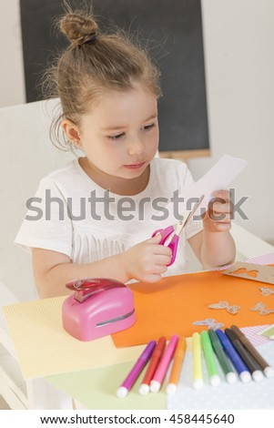 Beautiful little girl cutting paper with scissors on the art lesson class. Children education concept. Kids crafts