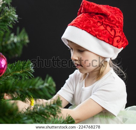 Beautiful little girl decorates the Christmas tree, black background - stock photo
