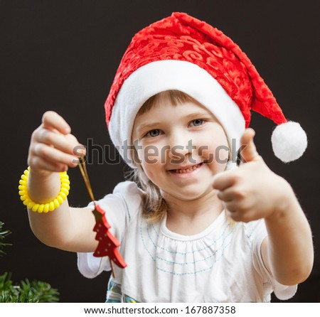 Beautiful little girl decorates the Christmas tree, dark background