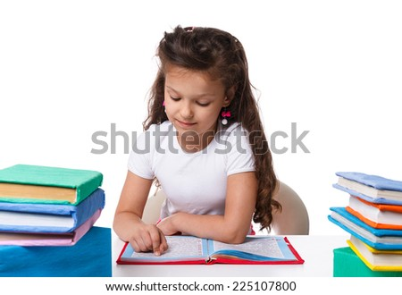Beautiful little girl doing homework sitting at table on white background