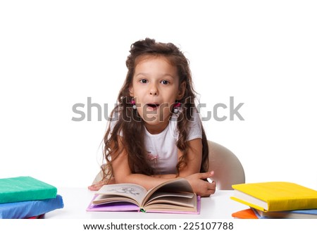 Beautiful little girl doing homework sitting at table on white background. emotions, surprise