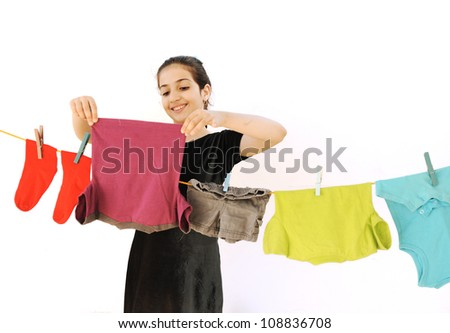 Beautiful little girl doing laundry - stock photo