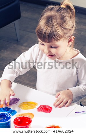 beautiful little girl draws a finger paints