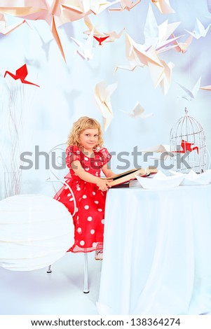 Beautiful little girl dreaming with her book and red paper bird in a birdcage. - stock photo