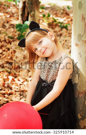 Beautiful little girl dressed as a cat with balloons in hands. Sweet smile, a tender look. - stock photo