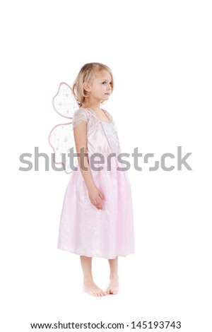Beautiful little girl dressed as a fairy in pink standing in bare feet posing sideways on a white background