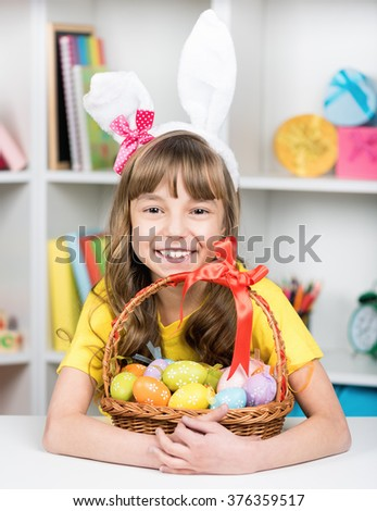 Beautiful little girl dressed in bunny ears with basket of Easter eggs at home