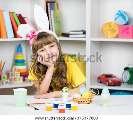 Beautiful little girl dressed in bunny ears with Easter eggs at home - stock photo