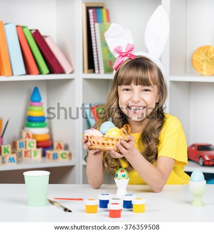 Beautiful little girl dressed in bunny ears with Easter eggs at home