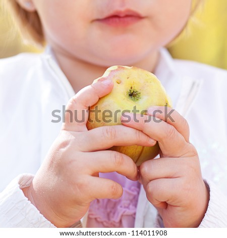 beautiful little girl eating apple in the autumn forest