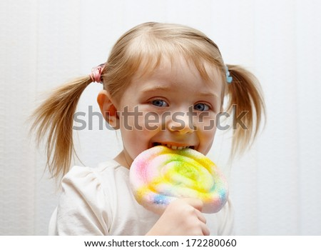 Beautiful little girl eating big colorful lollipop - stock photo