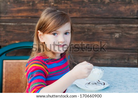 Beautiful little girl eating ice cream on a terrace on a nice day - stock photo