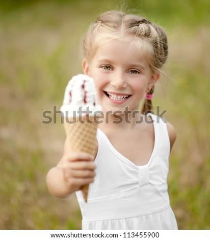 Beautiful little girl eats ice-cream in the summer - stock photo