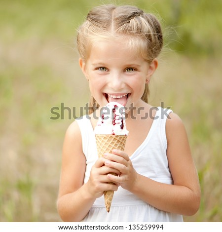 Beautiful little girl eats ice-cream in the summer - stock photo