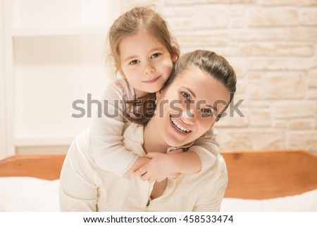 Beautiful little girl embracing her mother while sitting on the bed at home. Happy family concept. Mothers day. Mother and little lovely daughter. - stock photo
