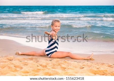 Beautiful little girl exercising on the beach outdoor