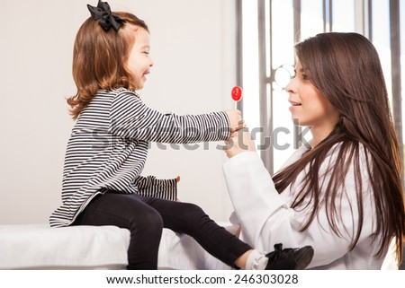 Beautiful little girl getting a lollipop for her good behavior at the doctor's office - stock photo