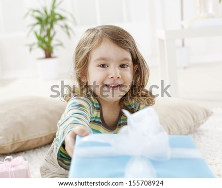 Beautiful little girl giving present box - stock photo